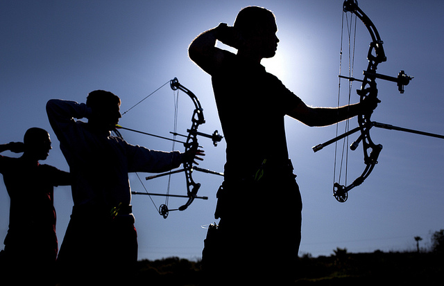 Three men shooting bows