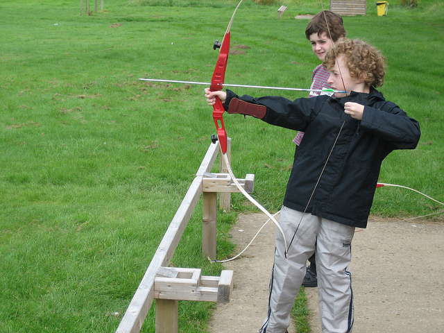 Boy shooting a recurve bow.